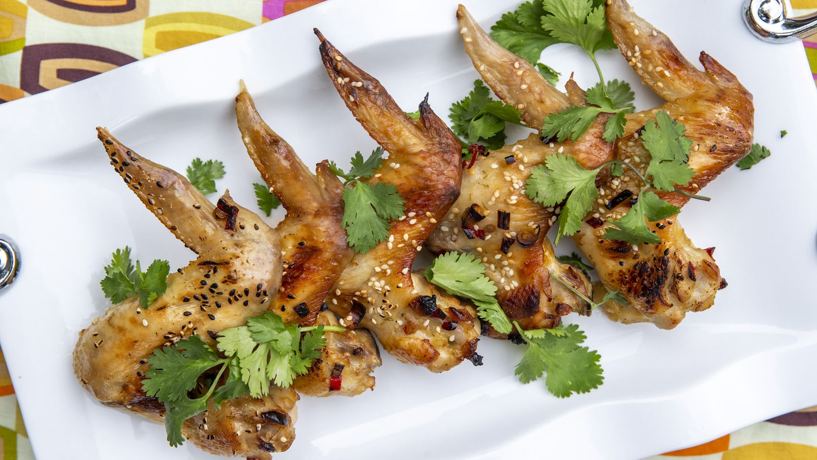 Glazed Sesame Chicken Wings Wings dressed with cilantro and sesame seeds