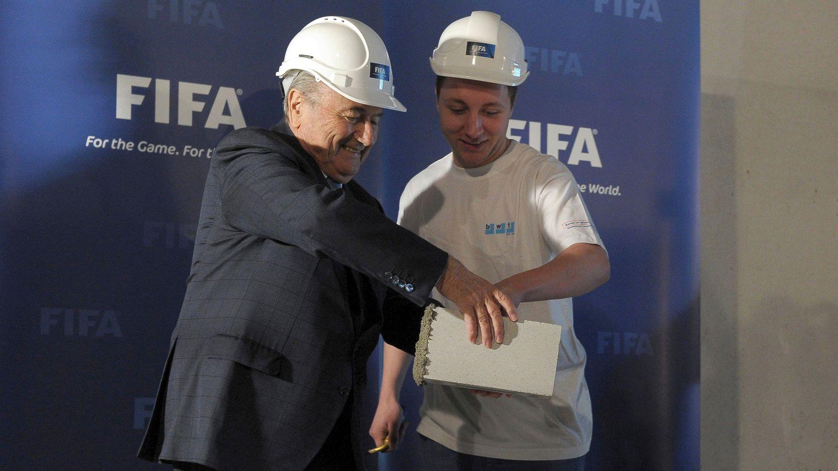El presidente de la  FIFA, Joseph  Blatter (izq), coloca el primer ladrillo en la construcción del Museo del Futbol, el 25 de abril de 2013.