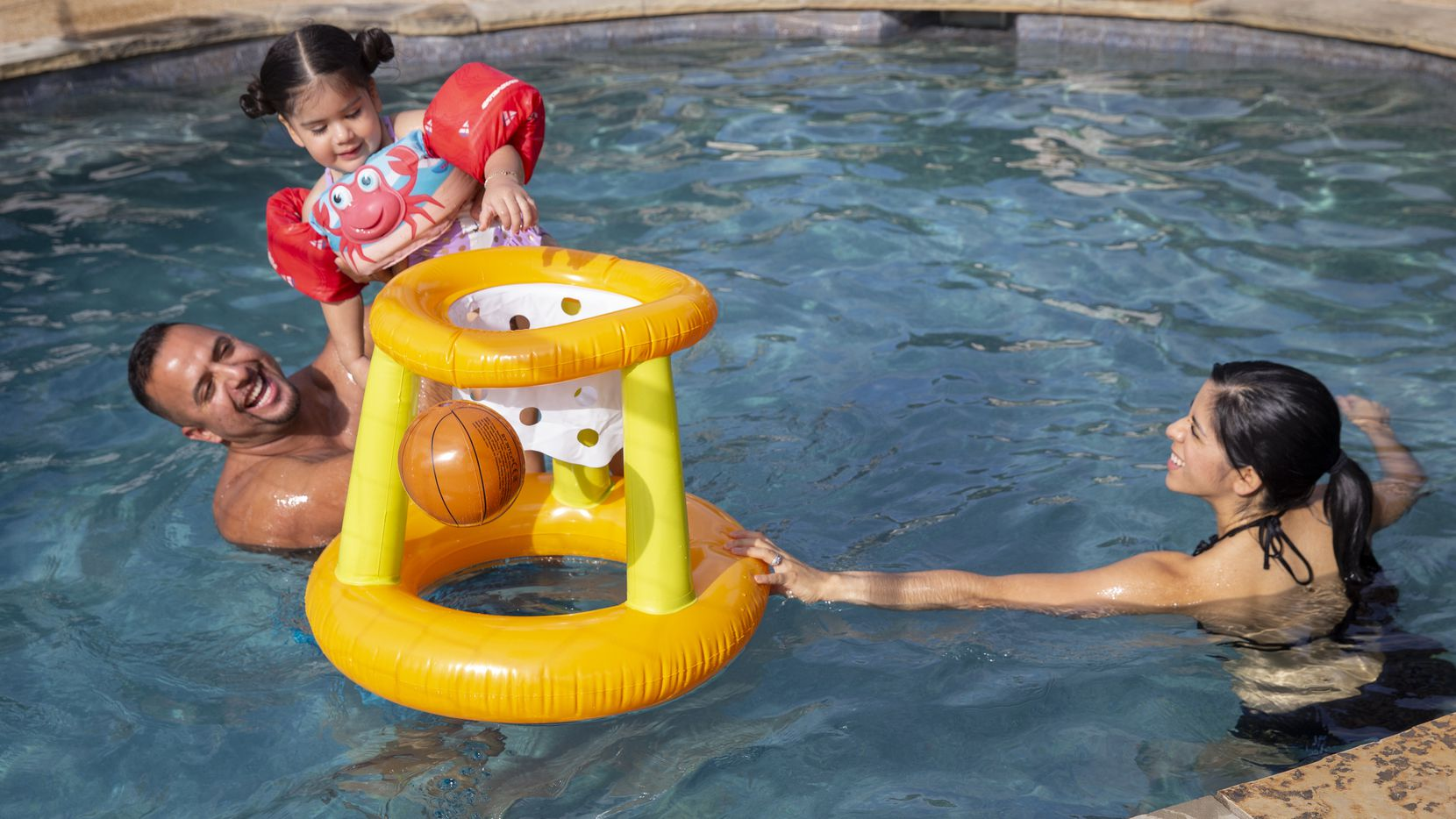 Tony Banda (left) holds his niece Giselle Mendoza, 2, as her mom Imelda Mendoza watches in a pool they rented using the Swimply app on July 26, 2020 in Waxahachie. Their sister Adriana Banda said she reserved the pool since her family wasn't able to have summer fun during quarantine.