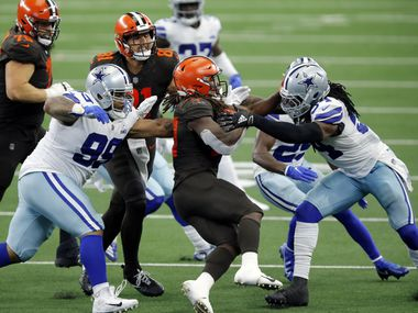 Dallas Cowboys defensive tackle Antwaun Woods (99) and middle linebacker Jaylon Smith (54) combine on a tackle of Cleveland Browns running back Kareem Hunt (27) during a third quarter run at AT&T Stadium in Arlington, Texas, Sunday, October 4, 2020. The Cowboys lost, 48-39.
