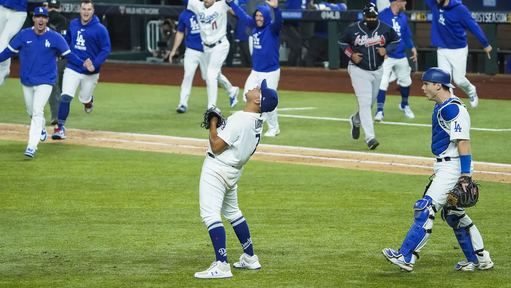 Los Angeles Dodgers pitcher Julio Urias (7) celebrates as the dugout empties after the final out of a 4-3 victory over the Atlanta Braves in Game 7 of a National League Championship Series at Globe Life Field on Sunday, Oct. 18, 2020.