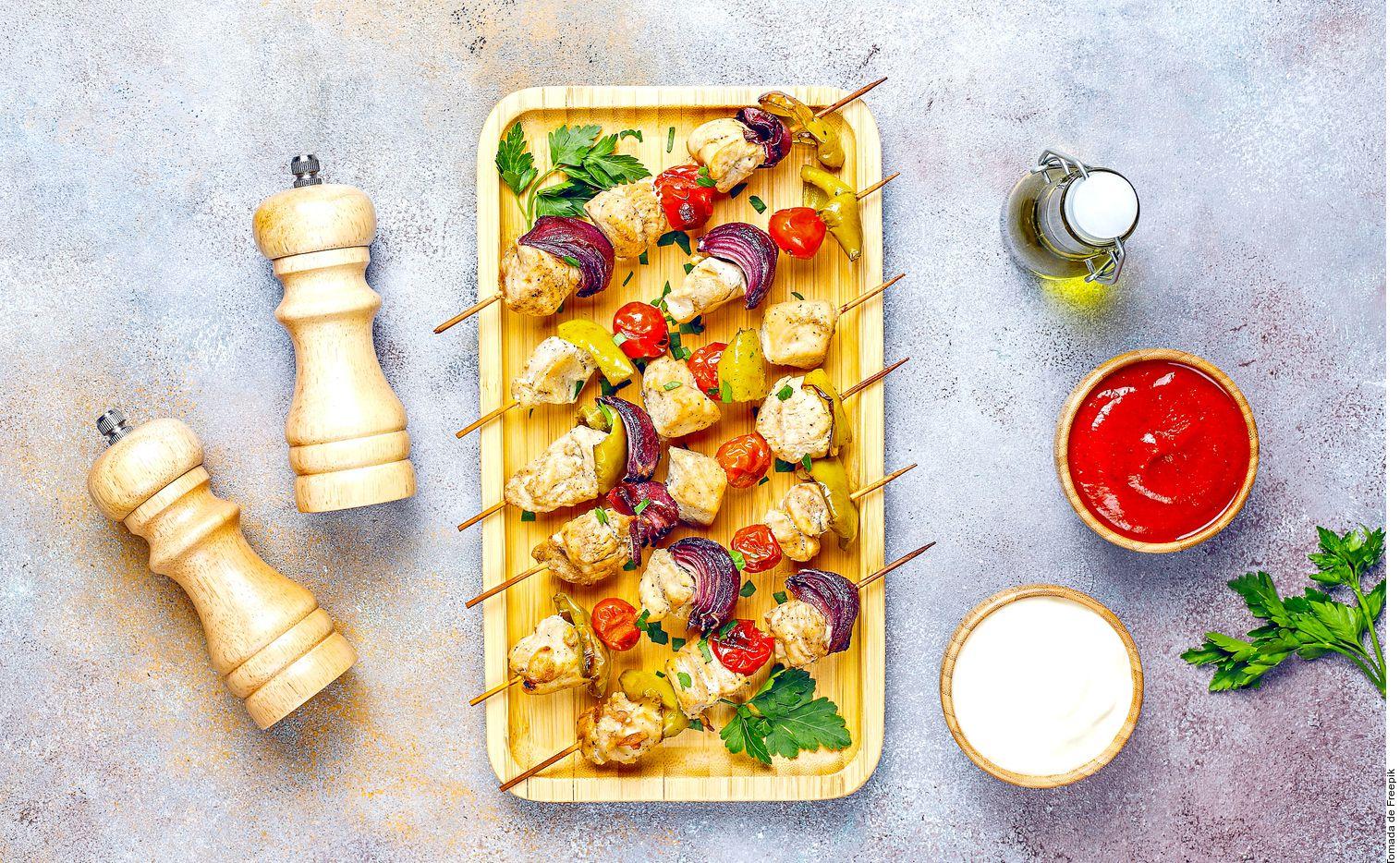 Las brochetas de pollo con verduras se logran al cortar el pollo en cubos. Mezclar el limón, la páprika y la mostaza. Marinar el pollo en la mezcla por mínimo 20 minutos.