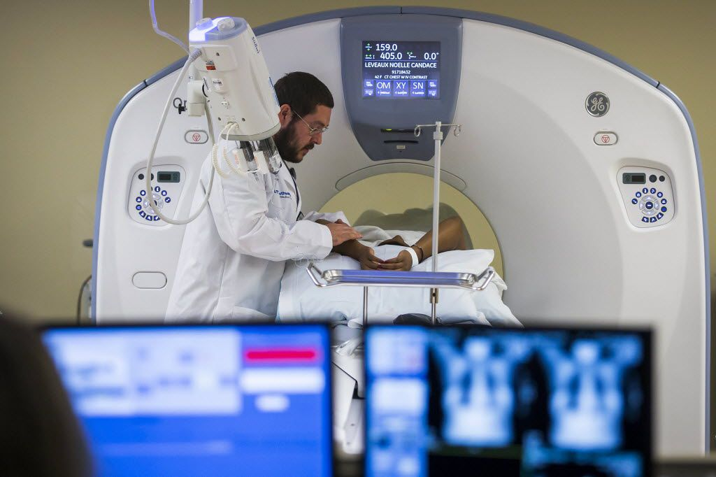 A breast cancer survivor has a CT scan with imaging technician Kenneth Colson at UT Southwestern Clinical Center at Richardson/Plano.
