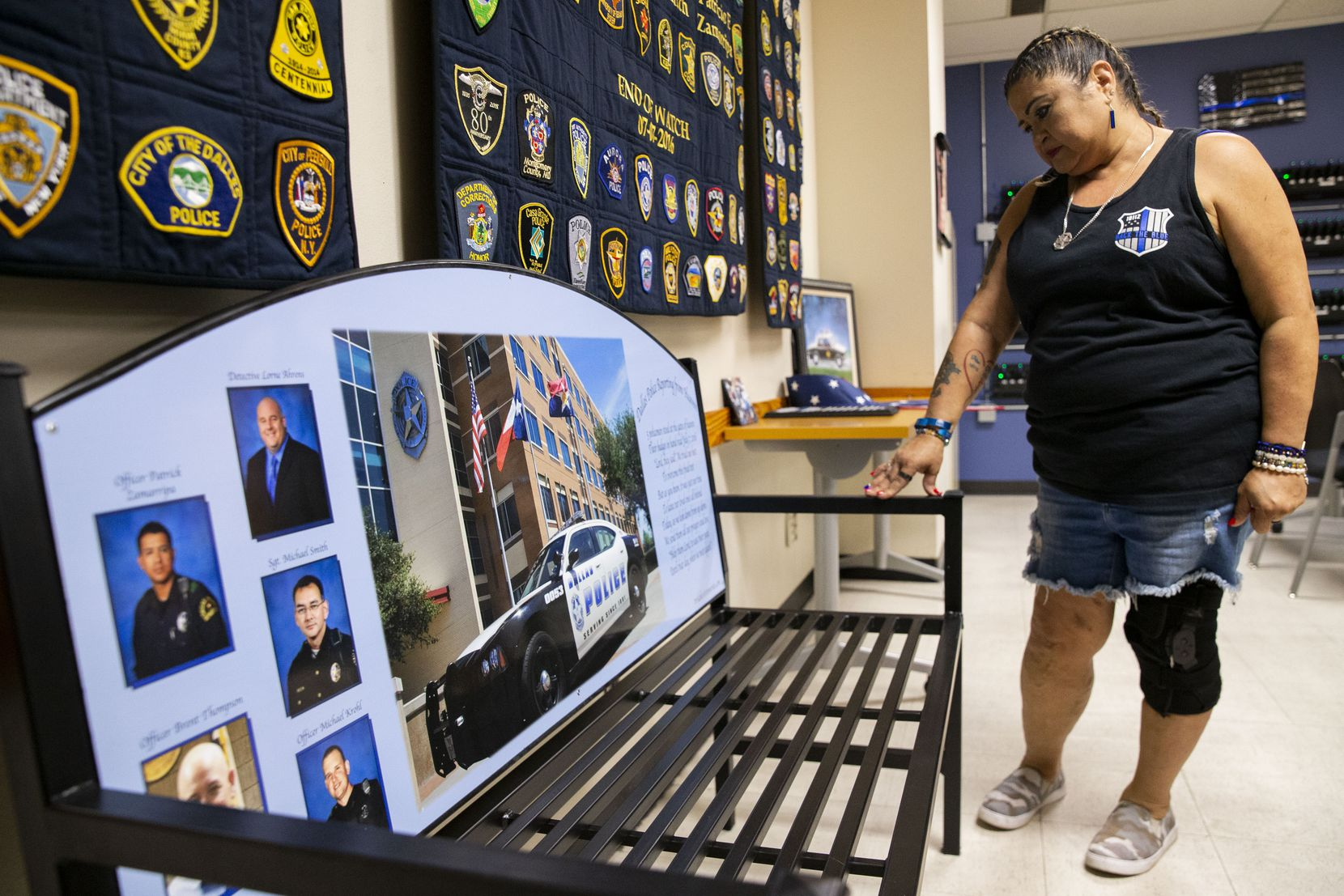 Valerie Zamarripa takes a moment while looking at a bench dedicated to the five Dallas police officers who were killed when a gunman ambushed a night of protests in downtown Dallas on July 7, 2016. She looks at the bench on Friday, July 2, 2021, at the Dallas Police Southwest Patrol division. Zamarripa's son, Patrick Zamarripa, was one of the five officers killed. (Juan Figueroa/The Dallas Morning News)