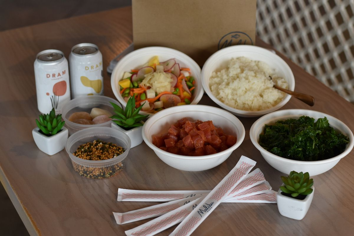 Malibu Poke offers family meal packs that include a choice of meat, sushi rice, kale, a bowl of veggie mix-ins and crunchy topping mix. It also includes 2 cans of DRAM CBD sparkling water and mochi ice cream.