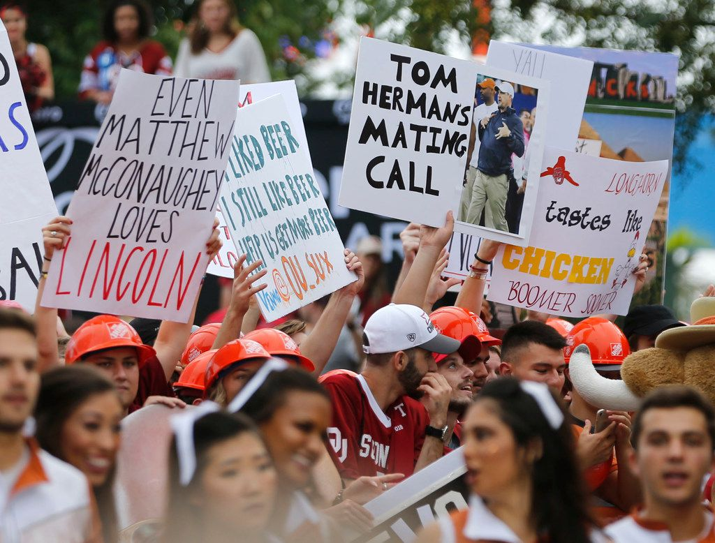Fans hold up signs as ESPN College GameDay broadcasts from the State Fair of Texas prior to the start of the UT vs OU football game at the Cotton Bowl in Dallas on Sunday, October 6, 2018. (Vernon Bryant/The Dallas Morning News)