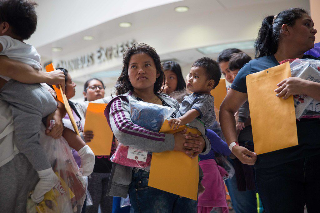 """Immigrants wait to head to a nearby Catholic Charities relief center after being dropped off at a bus station shortly after release from detention through the """"catch and release"""" immigration policy on Sunday in McAllen."""