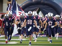 Aubrey quarterback Jaxon Holder (9) and tight end Wyatt Dyer (88) lead their team onto the field to face Terrell in a high school football game on Friday, Sept. 18, 2020, in Aubrey, Texas.