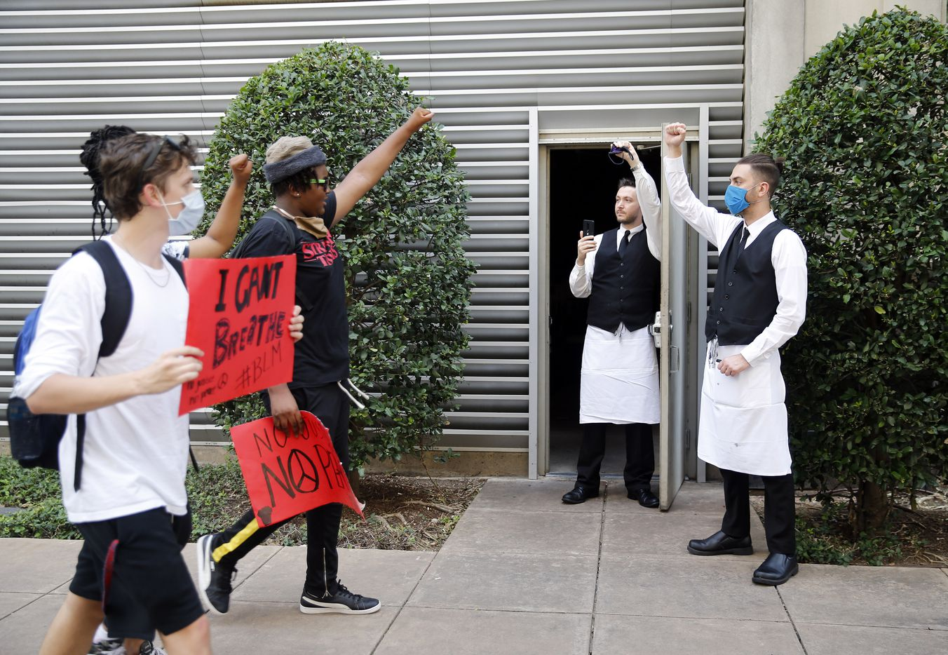 Employees of Perry's Steakhouse and Grill (right) came out of the restaurant in solidarity of marching protestors supporting Black Lives Matters in the Uptown area of Dallas, Tuesday, June 2, 2020. They gathered to protest the in-custody death of George Floyd.