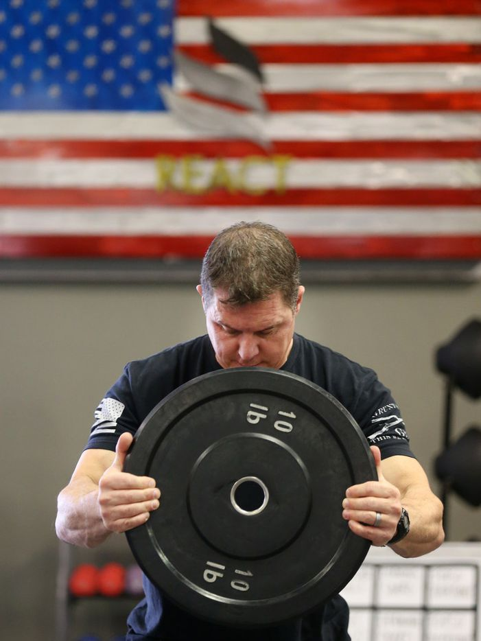 Addison Fire Chief David Jones holds a weight during a warmup at REACT gym in Addison. The gym is now offering a free injury prevention training program to Addison first responders.
