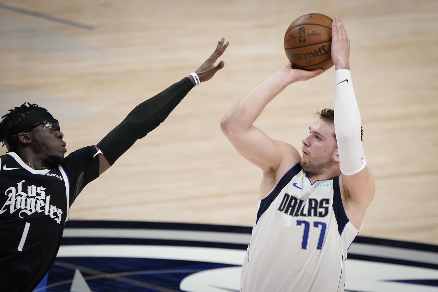 Dallas Mavericks guard Luka Doncic (77) shoots over LA Clippers guard Reggie Jackson (1) during the second quarter of an NBA playoff basketball game at American Airlines Center on Sunday, May 30, 2021, in Dallas.