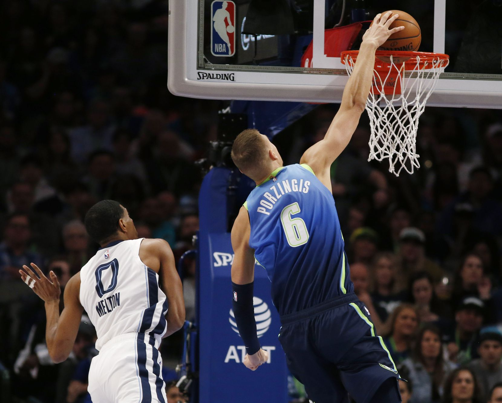 Dallas Mavericks forward Kristaps Porzingis (6) dunks the ball in front of Memphis Grizzlies guard De'Anthony Melton (0) during the first half of play at American Airlines Center in Dallas on Friday, March 6, 2020.