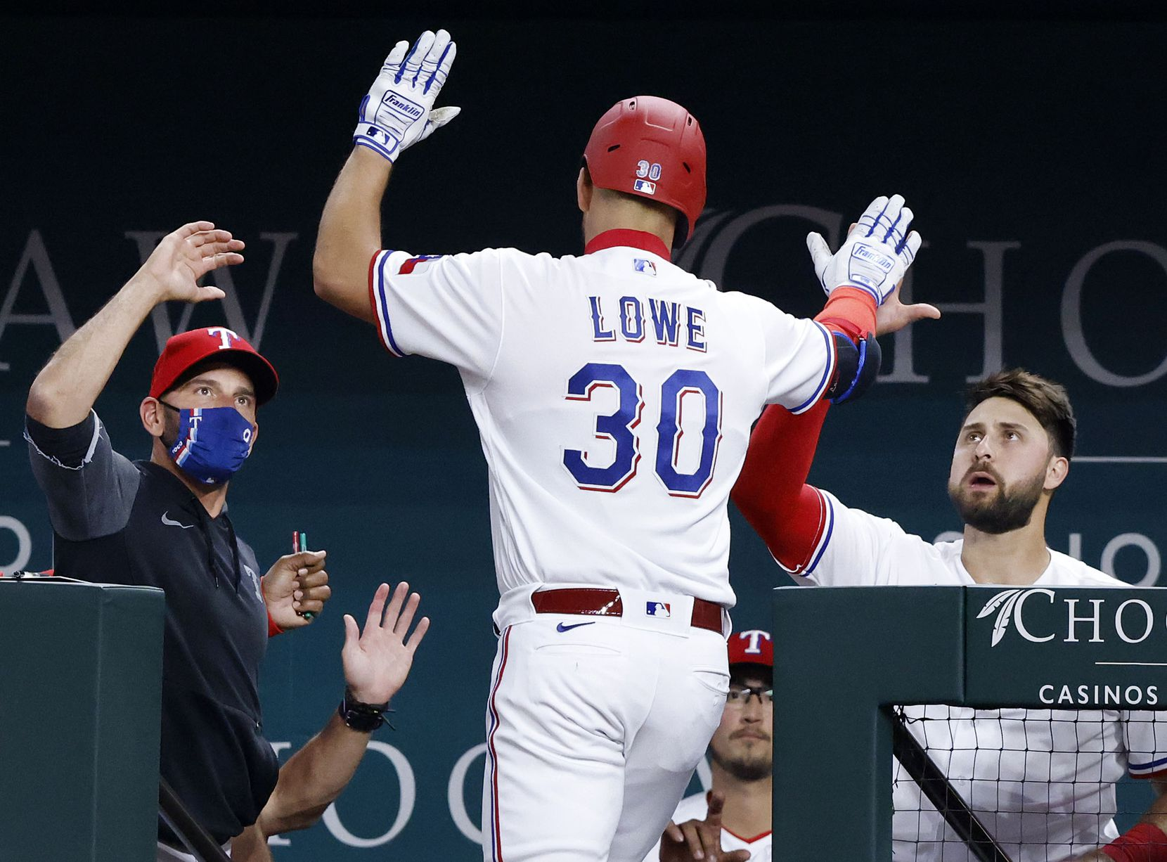 Texas Rangers Nate Lowe (30) is congratulated by teammate Joey Gallo (right) and manager Chris Woodward (left) after hitting a home run during first inning against the Toronto Blue Jays at Globe Life Field in Arlington, Tuesday, April 7, 2021. Loew scored Isiah Kiner-Falefa from third. (Tom Fox/The Dallas Morning News)