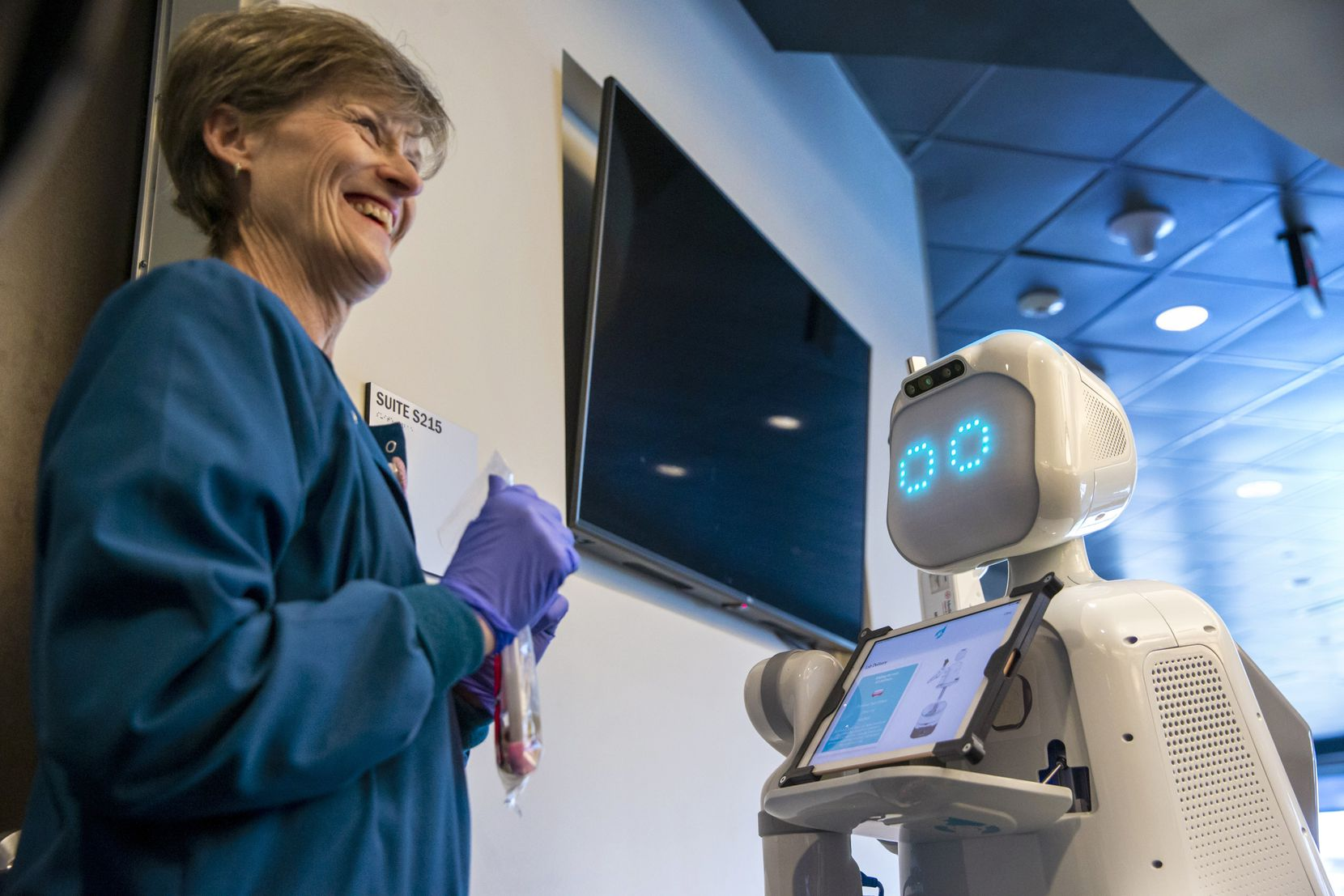 Medical technician Judy Erbacher retrieves a sample product from Moxi, a care assistant robot, during a specimen transfer demonstration at the Medical City Heart and Spine Hospital in Dallas on Friday, Feb. 14, 2020. The hospital is the first to use Austin-based Diligent Robotics robots as medical assistants.