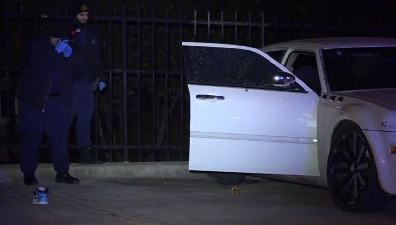 Dallas police photograph a car damaged by gunfire after a shooting Tuesday night in Far East Dallas.