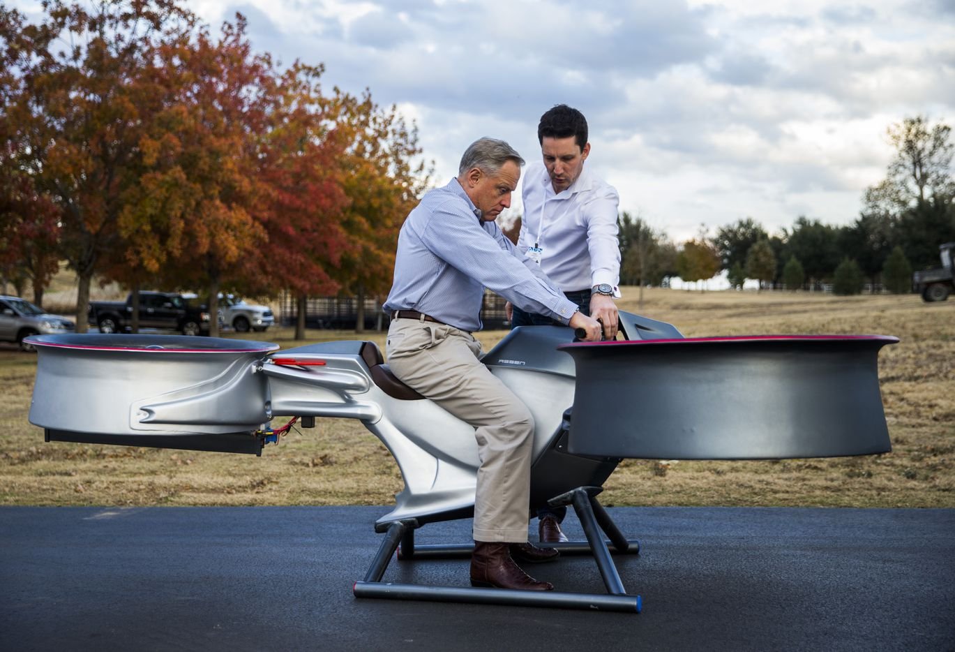 Ross Perot Jr. (left) takes a seat on a prototype of the Assen A2 Avenger sky bike with instructions from Assen Andonov (right), CEO and Founder of Assen Aeronautics, during an invitation-only summit at Circle T Ranch in Westlake, Texas. (Ashley Landis/The Dallas Morning News)