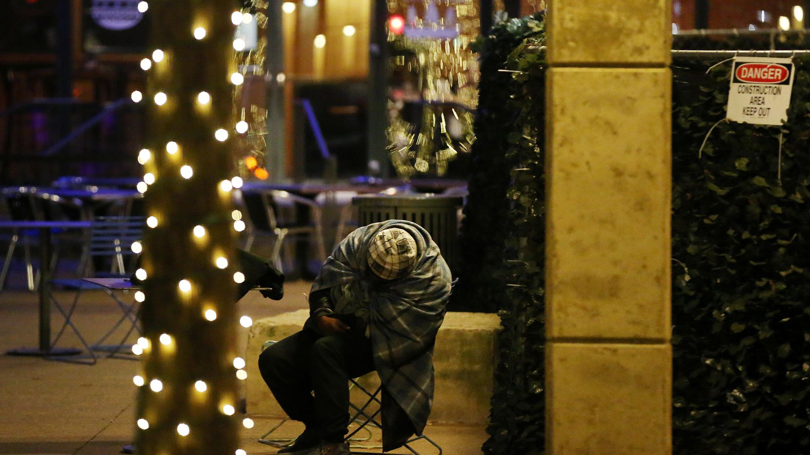 A homeless person slumped over in a chair in Pegasus Plaza in downtown Dallas on Dec. 31, 2017, as frigid temperatures dipping into the teens hit Dallas-Fort Worth.
