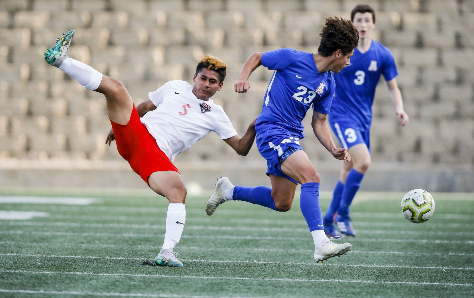 Allen junior midfielder Ayden Mendoza (23) steals the ball from Rockwall-Heath senior midfielder Gabriel Anguiano (5) during the first half of a boys soccer Class 6A state semifinal at Mesquite Memorial Stadium in Mesquite, Tuesday, April 13, 2021. (Brandon Wade/Special Contributor)