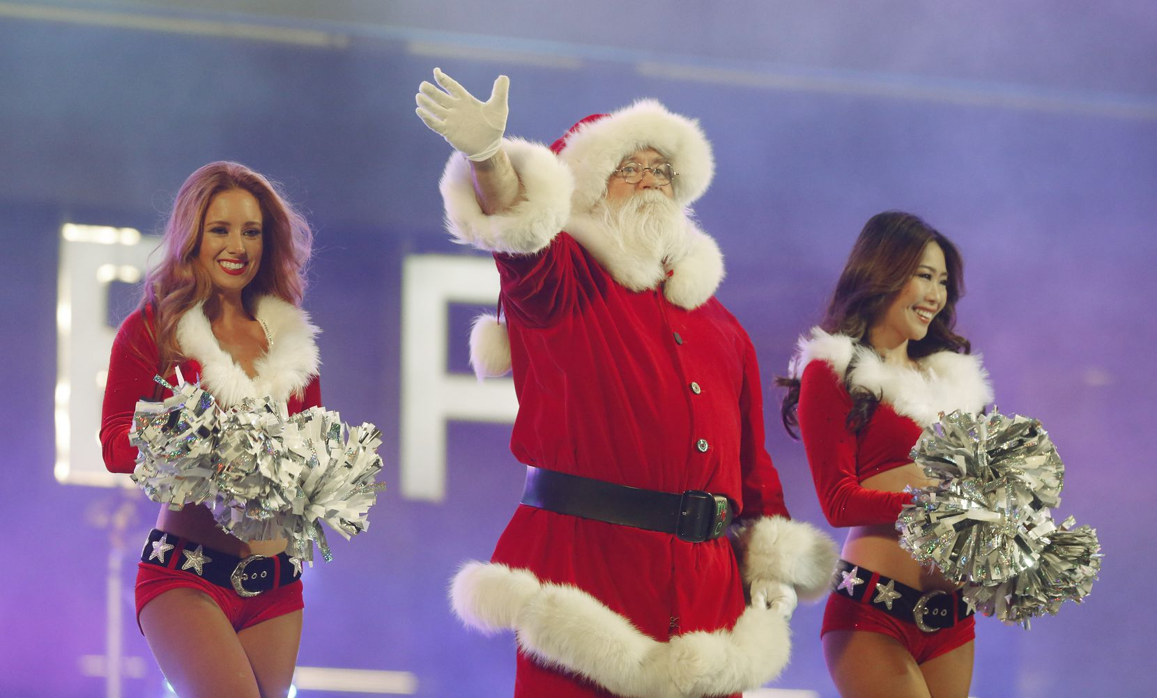 Santa Claus waves to the crowd during the Dallas Cowboys celebration of Christmas at The Star in Frisco.
