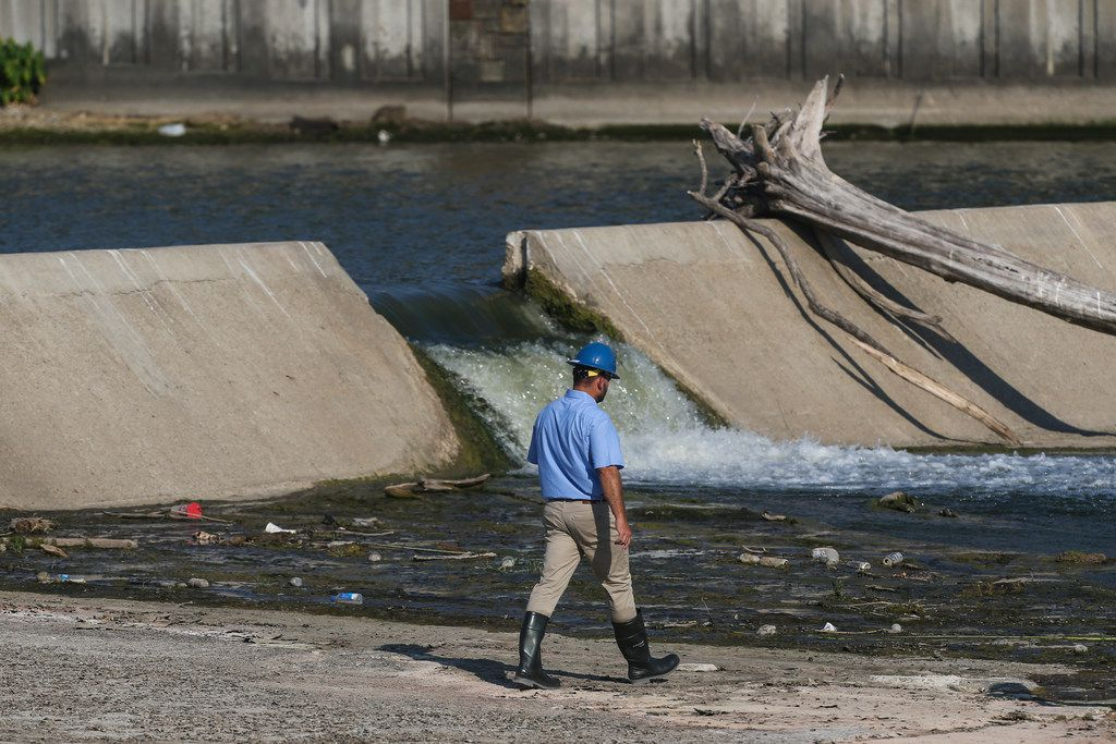 Officials survey the spillway at White Rock Lake on Thursday, July 25, 2019 in Dallas.