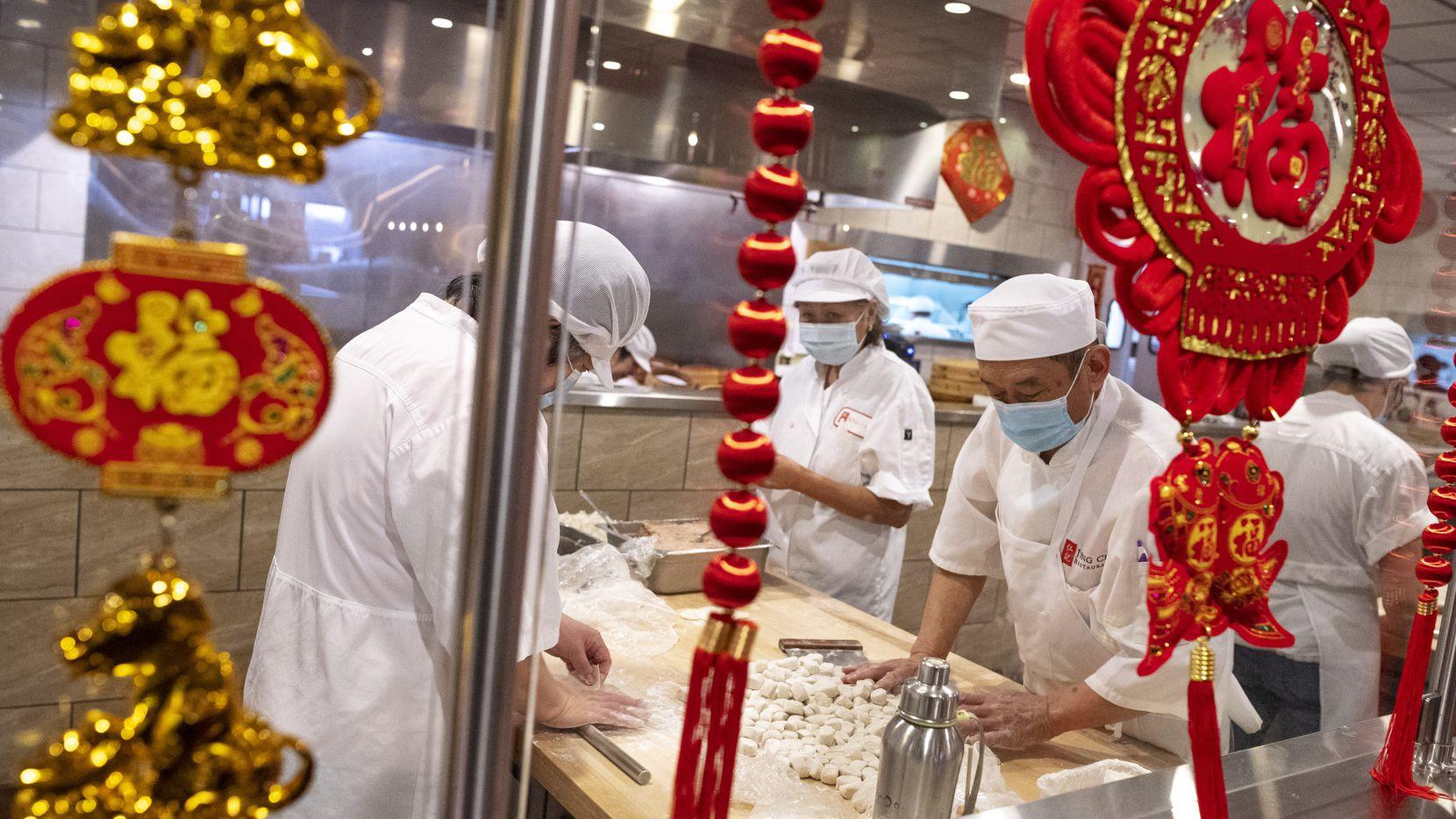 Yu Li (der.) y otros empleados hacen dumplings en Jeng Chi, un restaurante en Richardson que ha realizado desinfecciones permanentes para evitar casos de covid-19. Su negocio a domicilio ha proliferado.