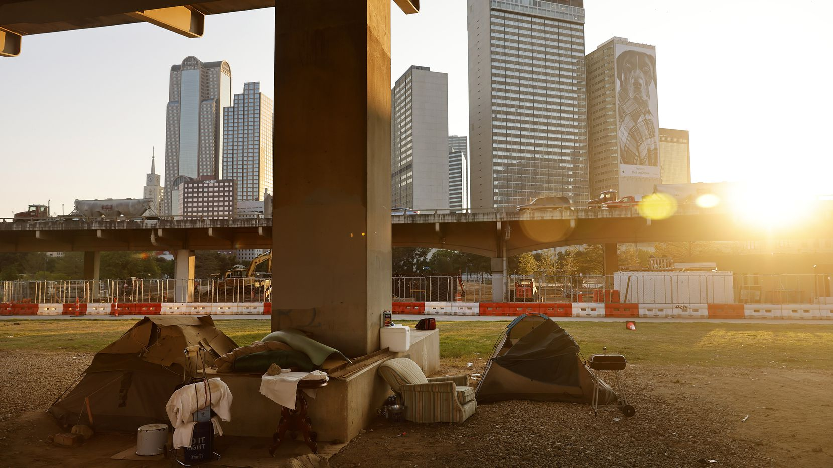 The sun sets behind a homeless encampment under the I-345 overhead in downtown Dallas, Thursday, August 26, 2021.(Tom Fox/The Dallas Morning News)