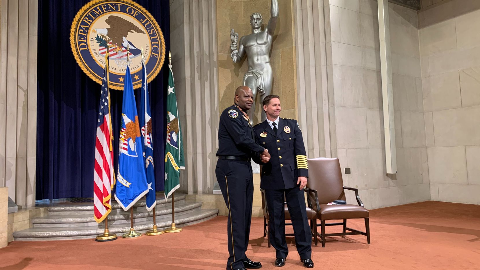 Irving Police Officer Jon Plunkett (left) shakes hands with Irving Police Chief Jeff Spivey (right) following a ceremony where Plunkett was given the Attorney General's Award for Distinguished Service in Policing on Dec. 3, 2019, at the Department of Justice in downtown Washington, D.C.