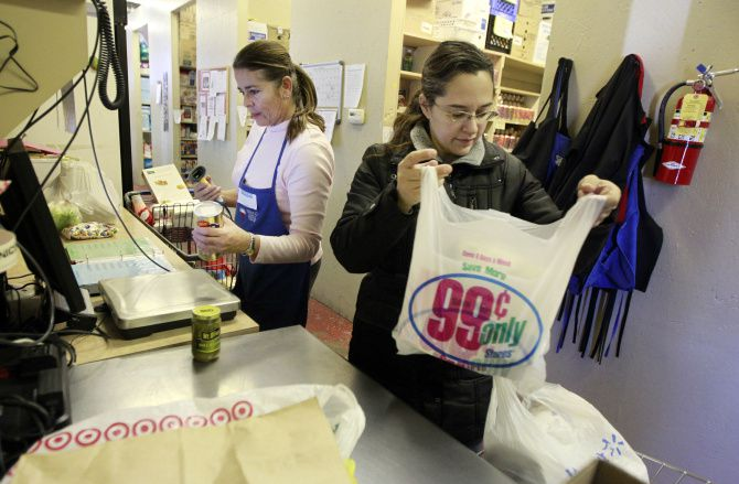 Anna Neal of Frisco, right, gets help from volunteer Sara Lempke as she checks out at the Frisco Family Services Center food pantry.
