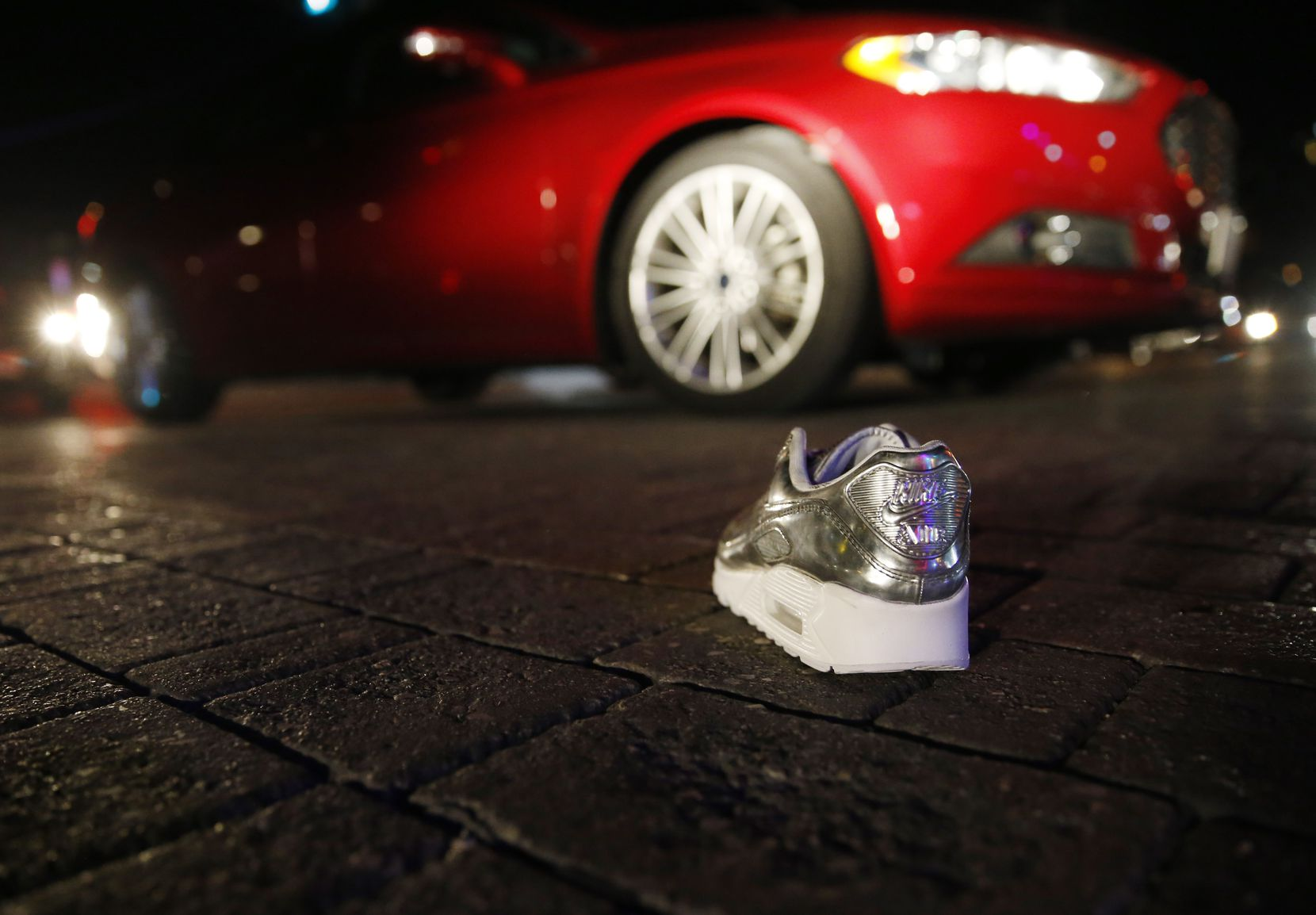 A lone shoe from Sneaker Politics sits in the middle of Main Street in Deep Ellum east of downtown Dallas. Looters raided the store and caused thousands of dollars in damage, shop manager Kellen Daniel said.