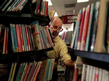 Charles David Smith puts books away at the North Oak Cliff Branch Library in this file photo.