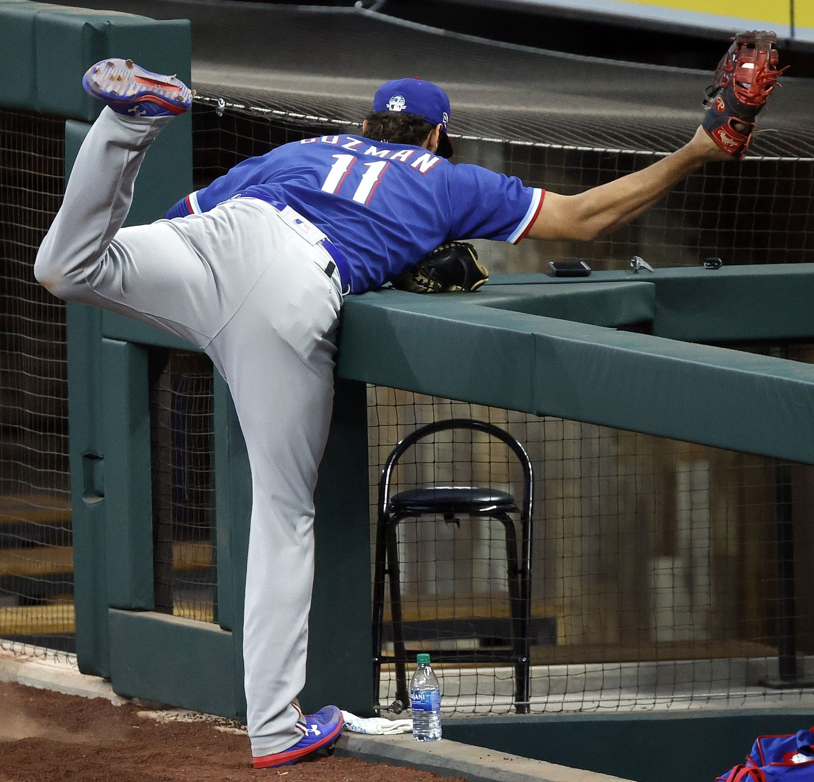 Texas Rangers first baseman Ronald Guzman reaches over the photo well railing, snaring a fly ball during a simulated game at Summer Camp inside Globe Life Field in Arlington, Texas, Thursday, July 9, 2020. (Tom Fox/The Dallas Morning News)
