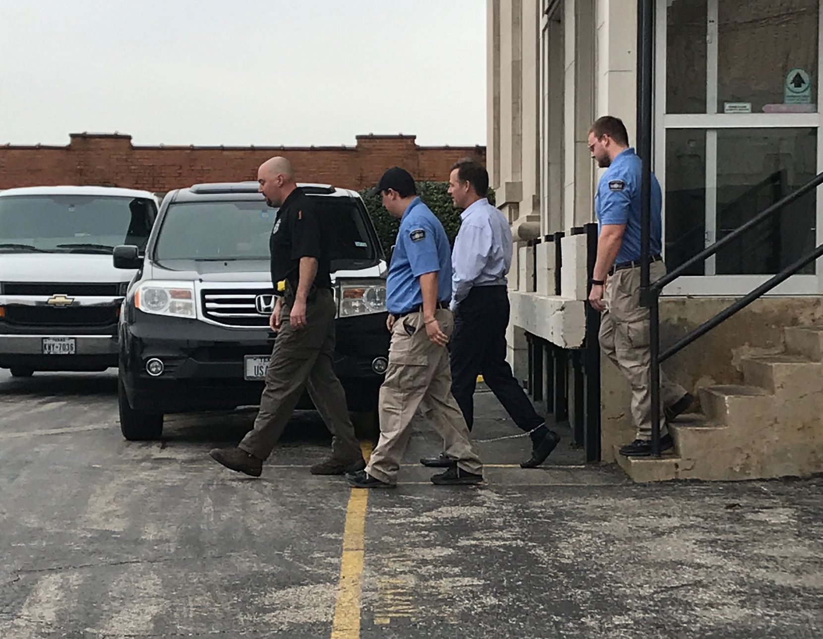 Mark Jordan (second from right) left the Sherman federal courthouse in handcuffs and shackles after being found guilty in March. He was later released from custody.