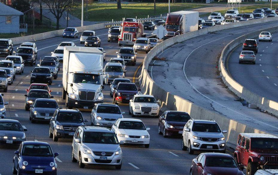 Eighteen-wheelers and other vehicles travel at a reduce speed due to traffic traveling northbound and southbound on Interstate-35.