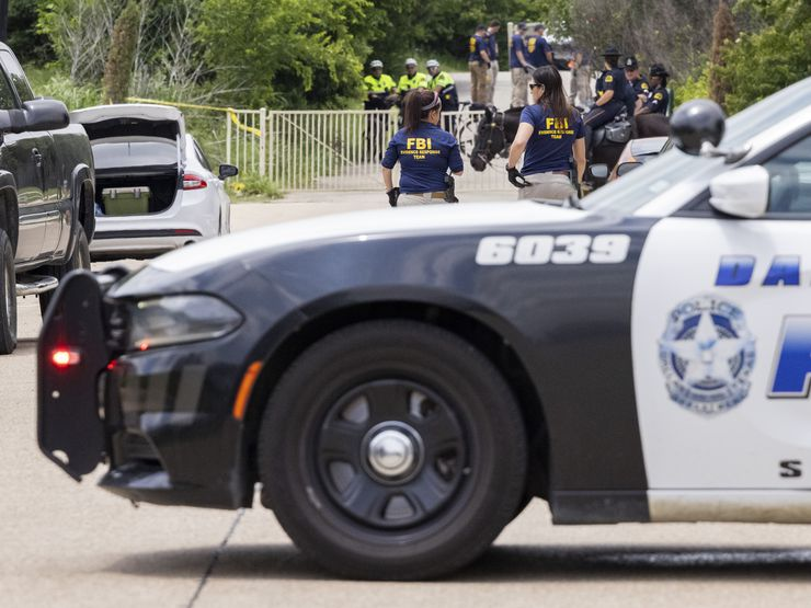 Dallas police and the FBI work the scene where a toddler boy was found dead early Saturday, May 15, 2021.