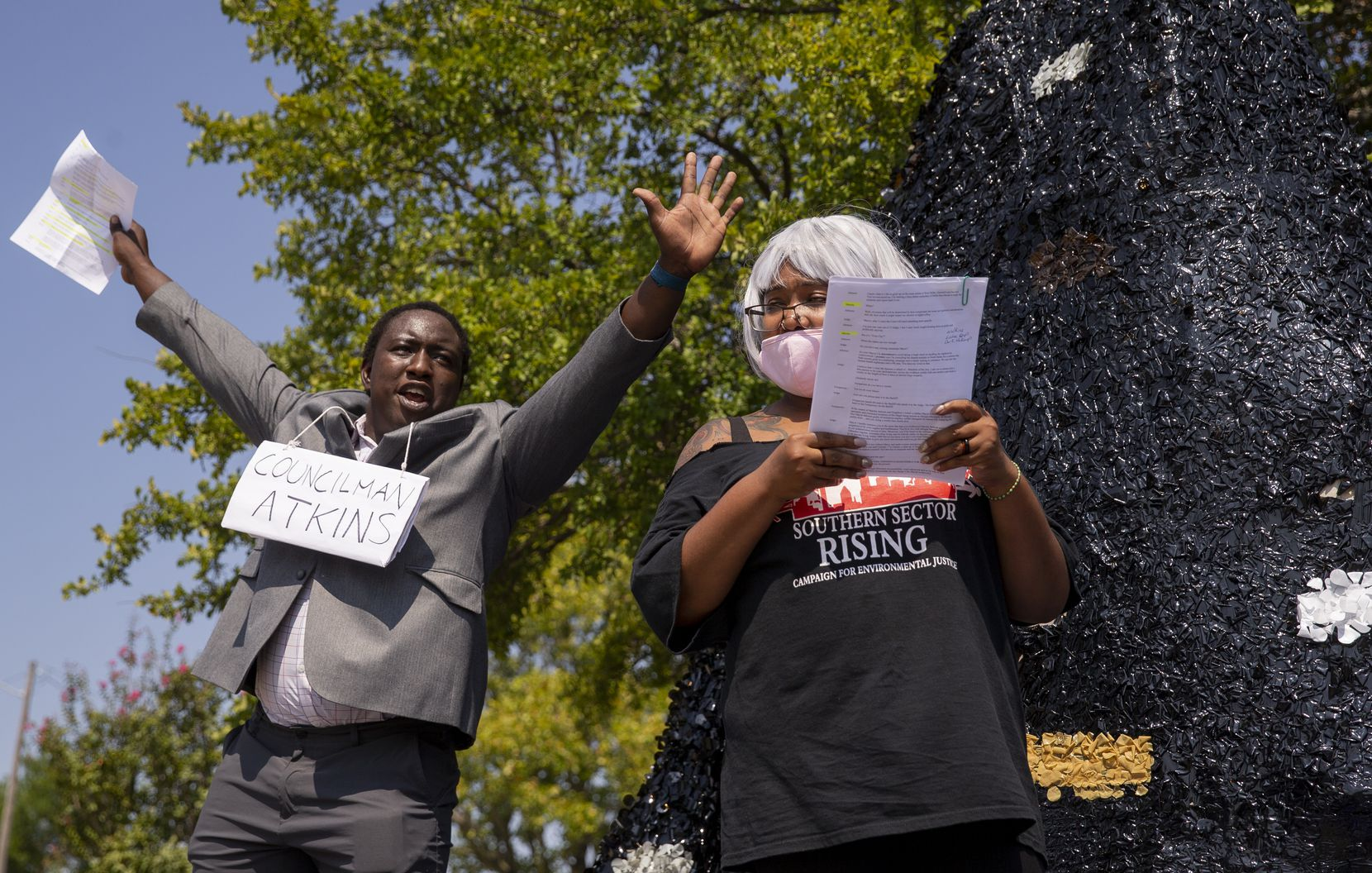 Simba Musarurwa (left) as Dallas City Council member Tennell Atkins and Misti Oquinn as Marsha Jackson perform a mock trial by Atkins' home during a parade of stops at city leaders' residences.