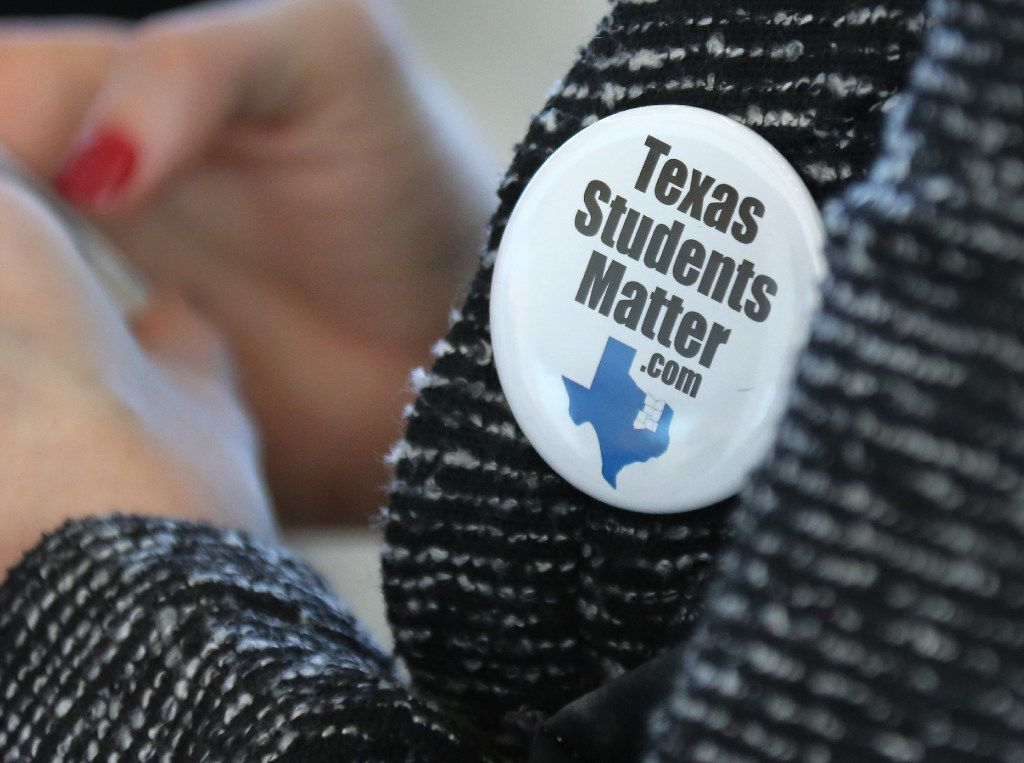 """Dallas area superintendents and trustees wear """"Texas Students Matter"""" buttons before a discussion on the state's A-F grading system."""