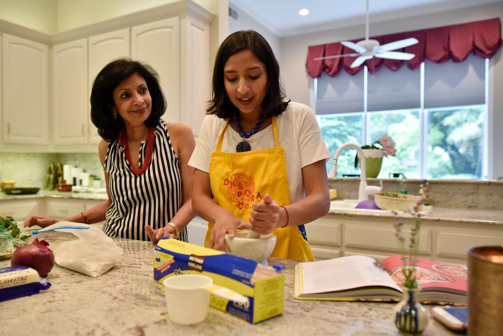 Priya Krishna (right) and her mother Ritu Krishna prepare dishes of roti and paratha at Priya's family home in Dallas.