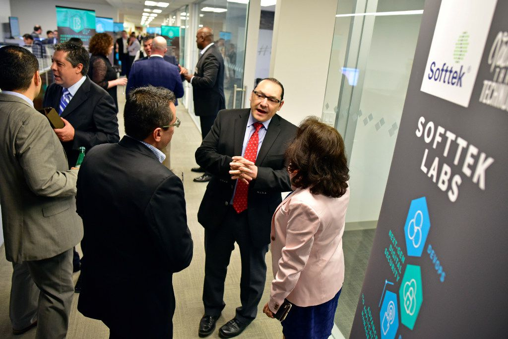 Consul General of Mexico Francisco de la Torre, center, speaks with Softtek vice president of logistics and transportation Melik Hernandez, left, and Betty Cardiel director of governance and contract during a celebration of the company's grand opening of it's U.S. headquarters in Addison on Wednesday. . Ben Torres/Special Contributor