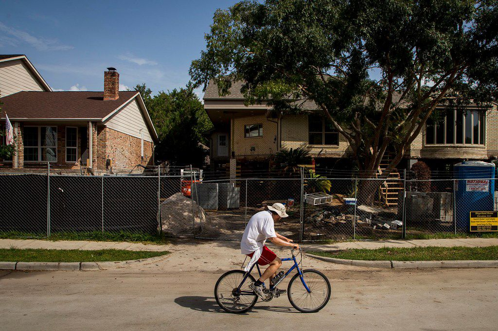 A cyclist rides past houses being raised as part of home elevation efforts in the Meyerland neighborhood, a few blocks from Brays Bayou, on Saturday, Aug. 11, 2018, in Houston. The area was flooded due to Hurricane Harvey.  (Smiley N. Pool/The Dallas Morning News)