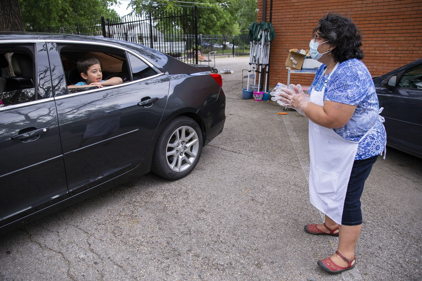 """Debbie Orozco Solis with the Voice of Hope Ministries chats with a client and her 5-year-old son after they received their food box. Solis is trying to help everyone she can because, she says, """"they are out of work and worried they won't be able to pay their taxes."""""""