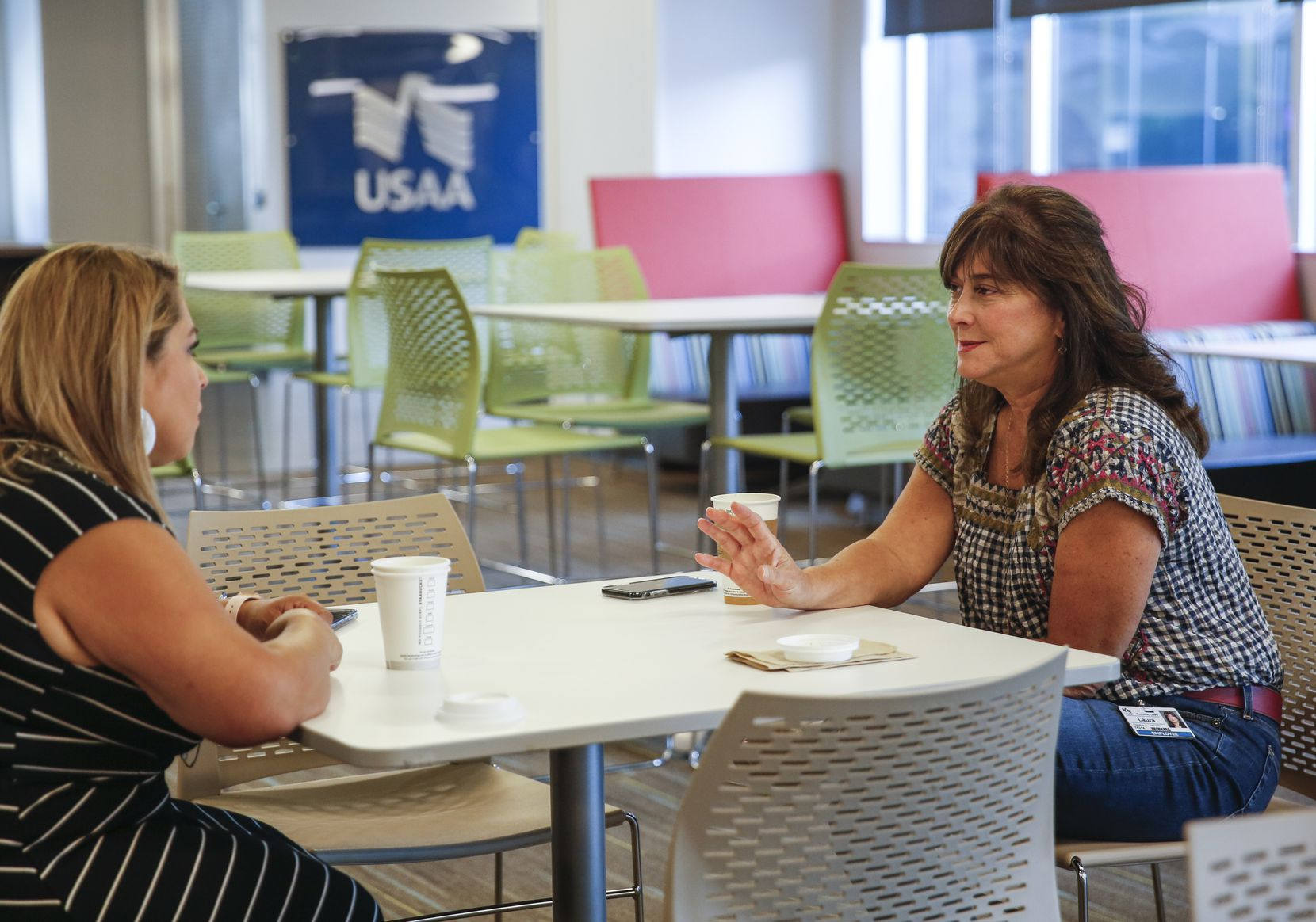 Alycia O'Leary, left, and Laura Radcliffe chatted in a cafeteria area at USAA in August.