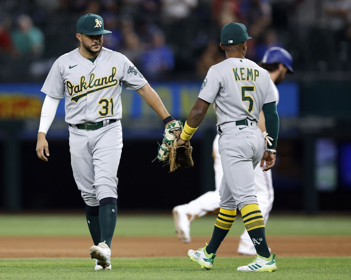 Oakland Athletics shortstop Vimael Machin (31) and second baseman Tony Kemp (5) tap gloves after getting Texas Rangers runner Charlie Culberson (2) on an infield hit during the ninth inning at Globe Life Field in Arlington, Saturday, August 14, 2021.(Tom Fox/The Dallas Morning News)