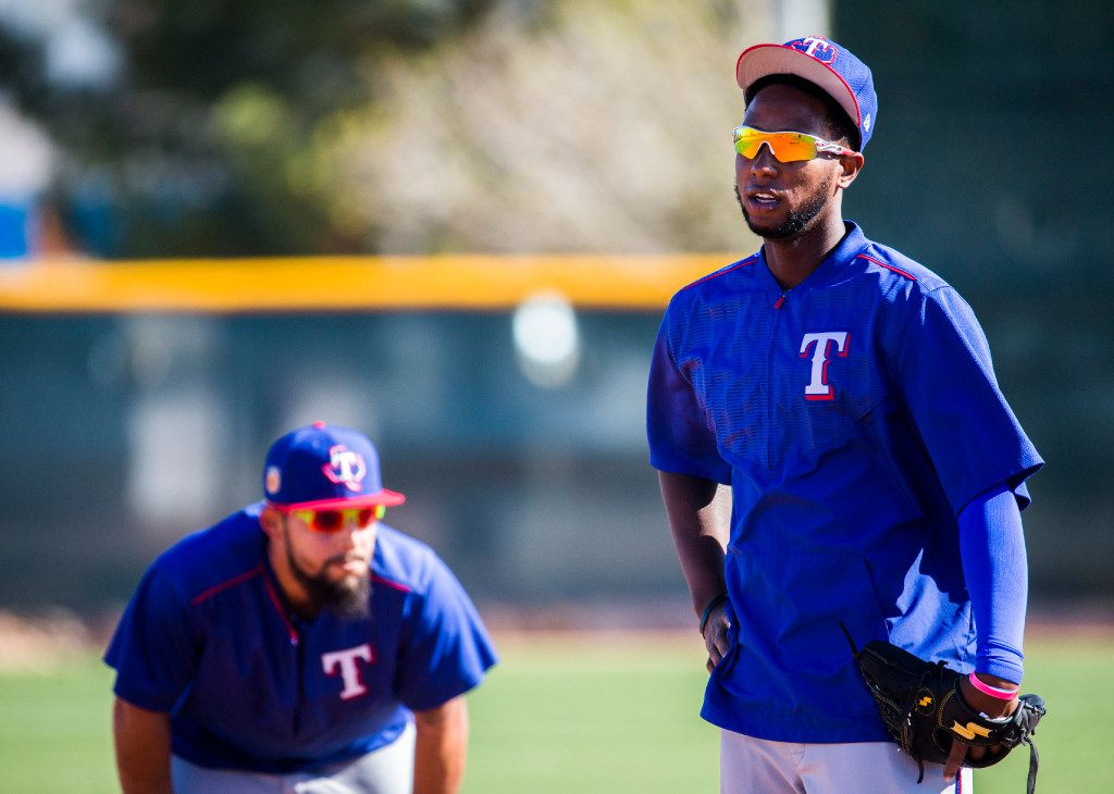 Texas Rangers third baseman Jurickson Profar (19, right) and second baseman Rougned Odor (12) take a breather after fielding balls in the outfield during a spring training workout at the team's training facility on Thursday, February 23, 2017 in Surprise, Arizona. (Ashley Landis/The Dallas Morning News)
