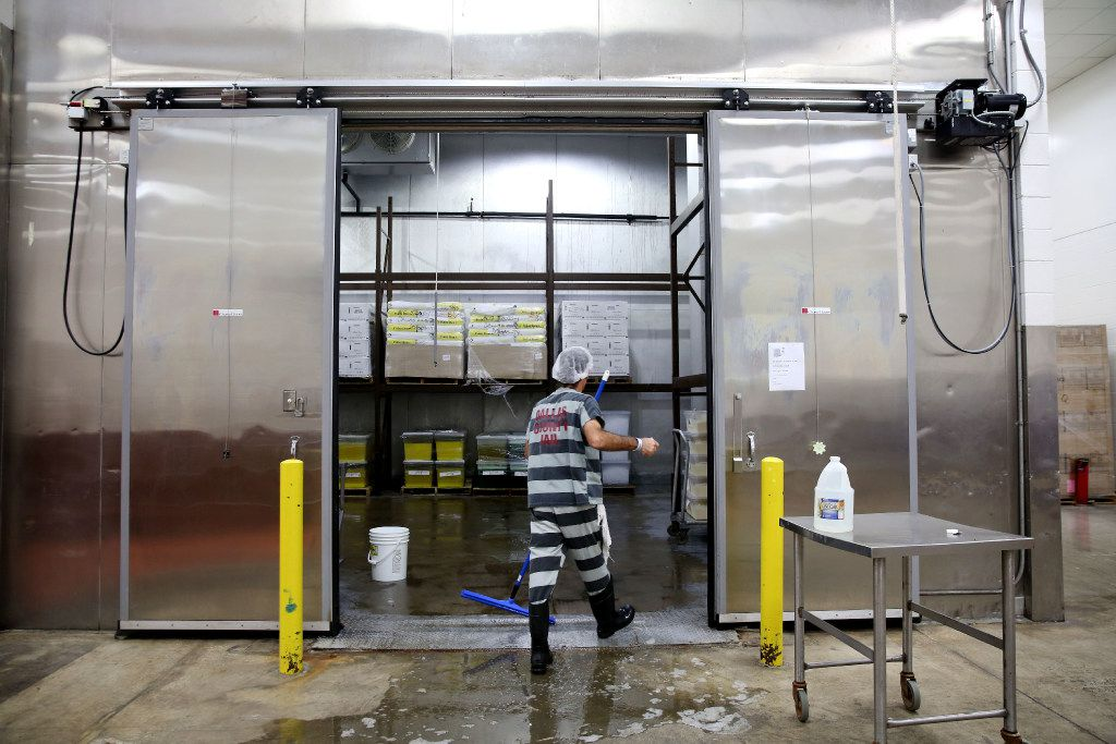 A Dallas County inmates cleans out a cooler at the Cook-Chill facility.