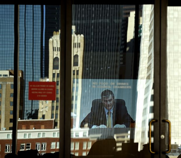 Dallas Mayor Mike Rawlings opens up the city council meeting in the reflection of the outer doors at Dallas City Hall November 12, 2014.