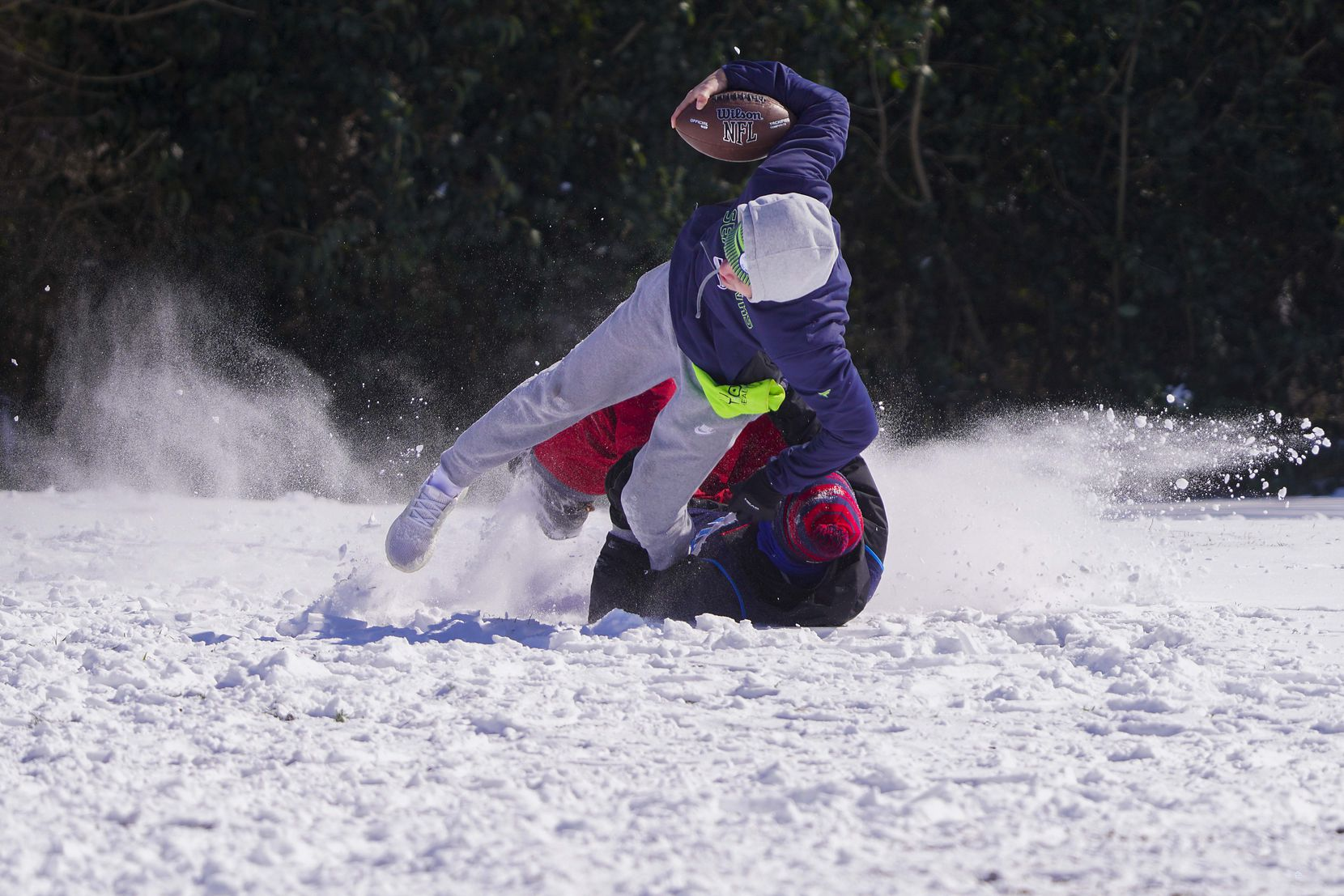 Andre Cavazos is brought down by Wesley Hart as they play football with other friends from J.J. Pearce High School at Prairie Creek Park after winter storm brought snow and freezing temperatures to North Texas on Monday, Feb. 15, 2021, in Richardson.  (Smiley N. Pool/The Dallas Morning News)