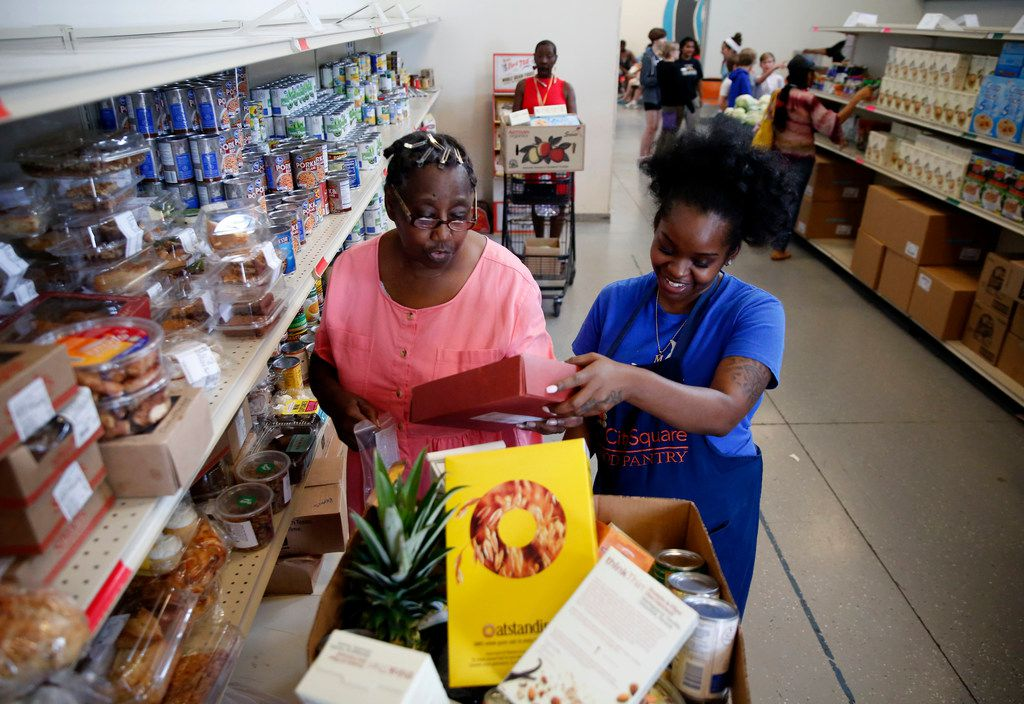 Volunteer Myree Hollins (right) helps client Ardell McNeal get groceries at the CitySquare food pantry in Dallas on June 13.