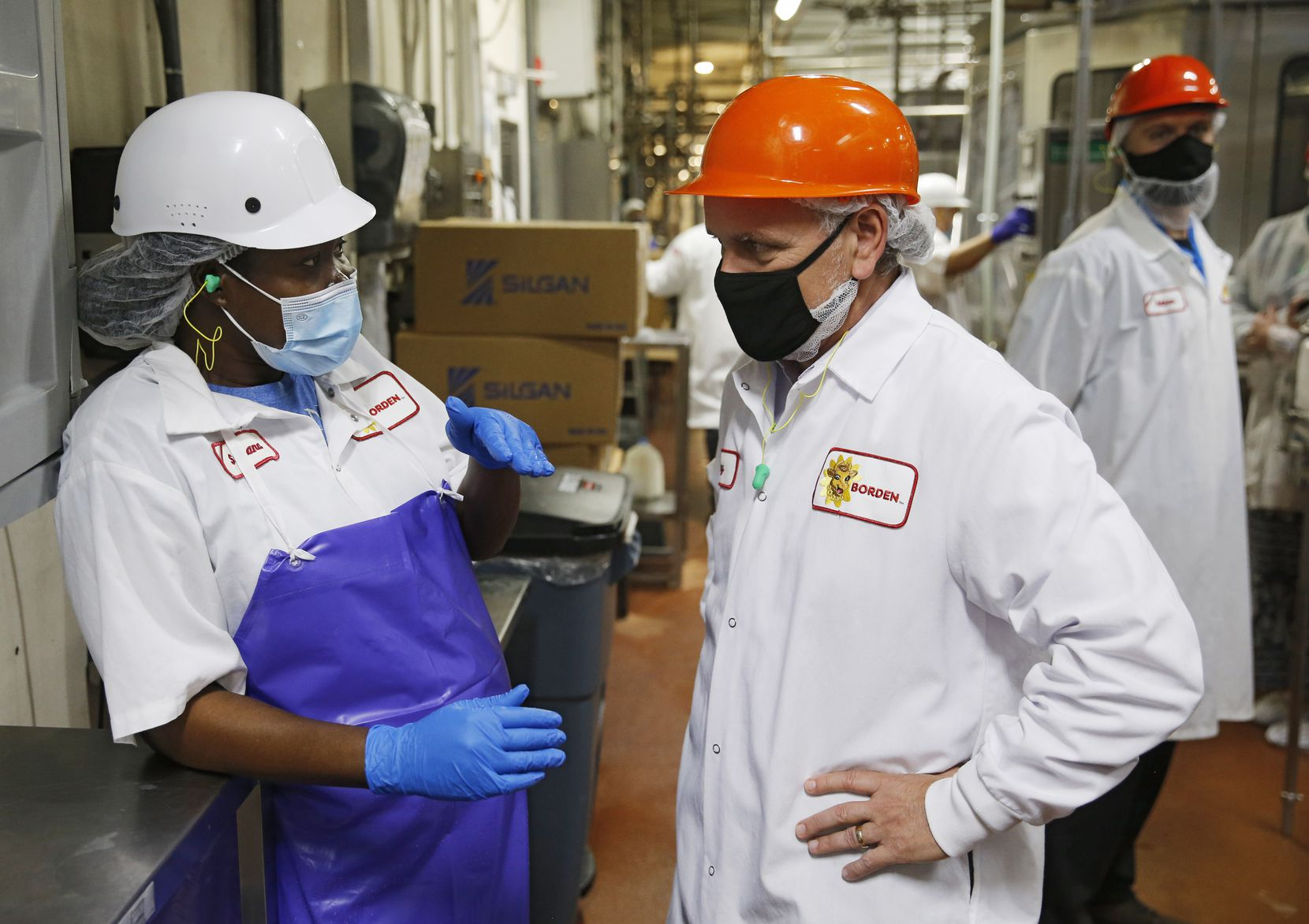 Borden employee Betty Anthony talks with CEO Tony Sarsam in the bottling area at Borden Dairy Co.