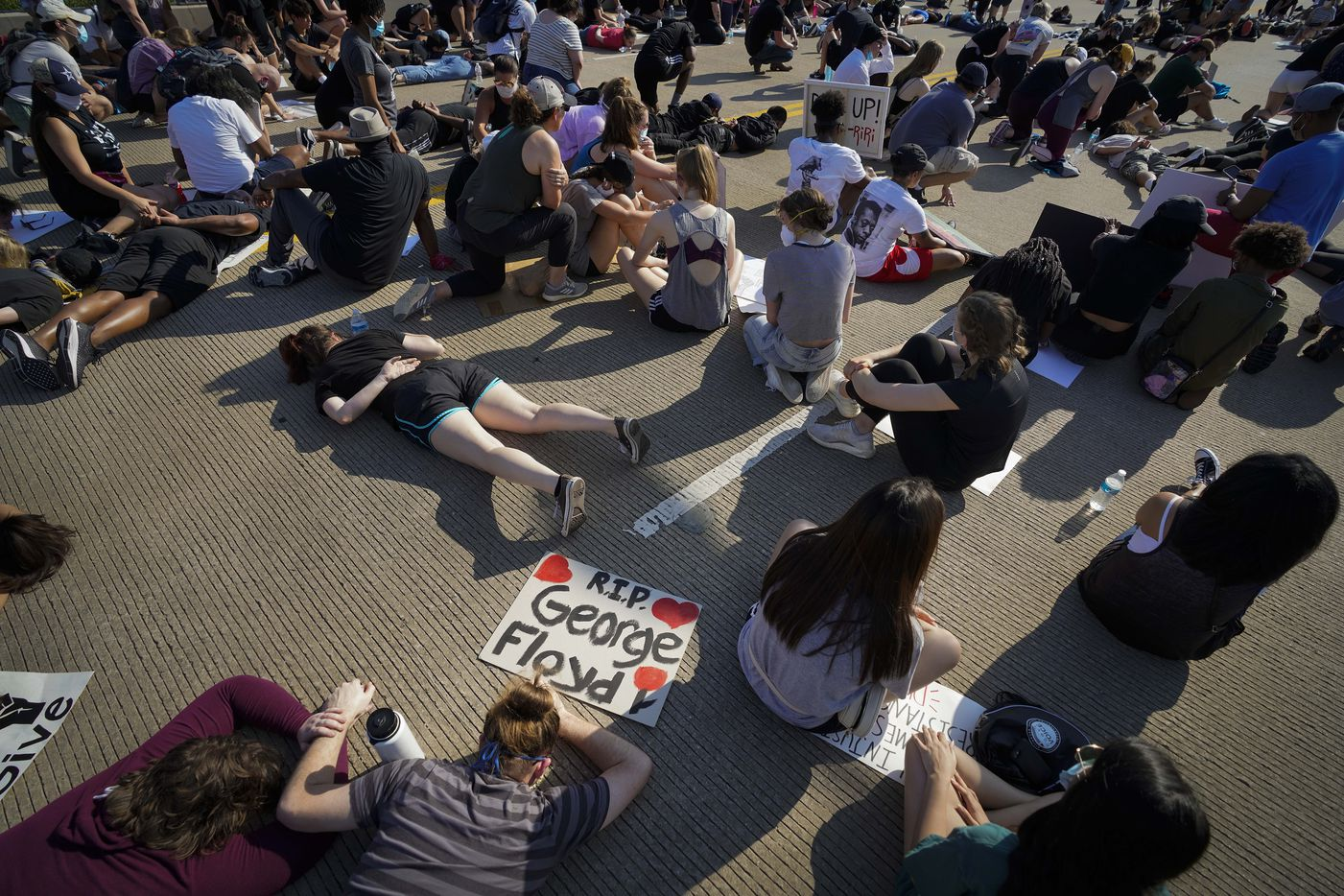 Demonstrators stop a march on the Arapaho Road bridge crossing Midway Road to kneel or lay down on the pavement in silence for 8 minutes and 46 seconds during a protest on Thursday, June 4, 2020, in Addison. Protests continued Thursday in the response to the death of George Floyd.