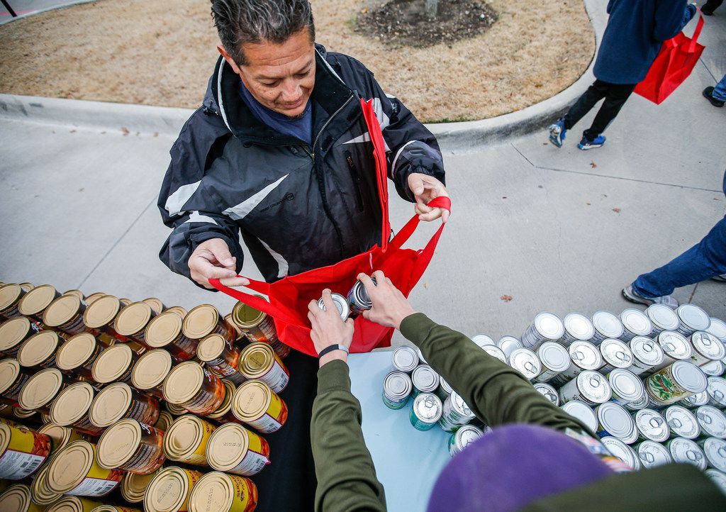 Brady Boozer, 12, places cans of green beans into Andy InocencioÕs bag at at the Texas Rangers MLB Youth Academy at Mercy Street Sports Complex in Dallas, Friday, November 22, 2019. The Texas Rangers Baseball Foundation donated turkeys, sides, and desserts to nearly 200 families for the Thanksgiving holiday.